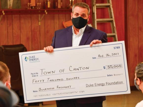 Duke Energy spokesman Jason Walls presents the Town of Canton with a $50,000 check on Aug. 26. Cory Vaillancourt photo