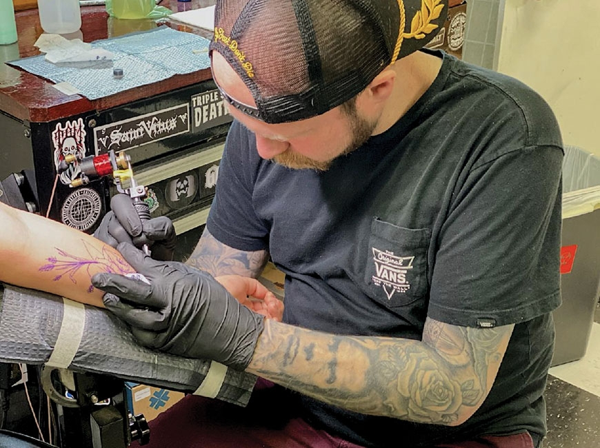 Robbie Crisp working on a new arm piece for a client at Born and Raised Tattoo parlor in Sylva. (photo: Garret K. Woodward)
