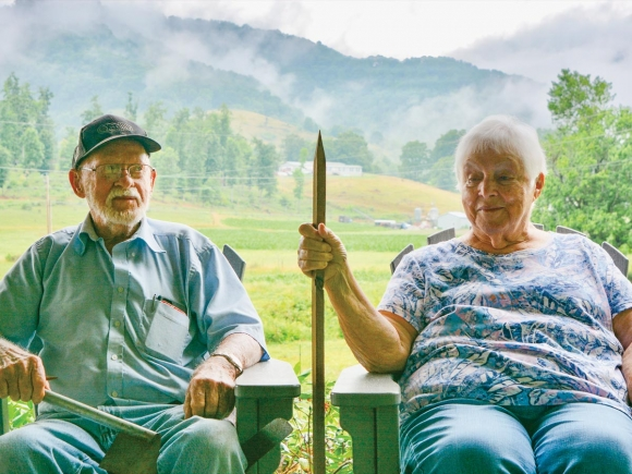 Ben Best (left) sits on the porch with wife Clarine, who's holding a spike of the sort used for tobacco harvesting. Cory Vaillancourt photo.