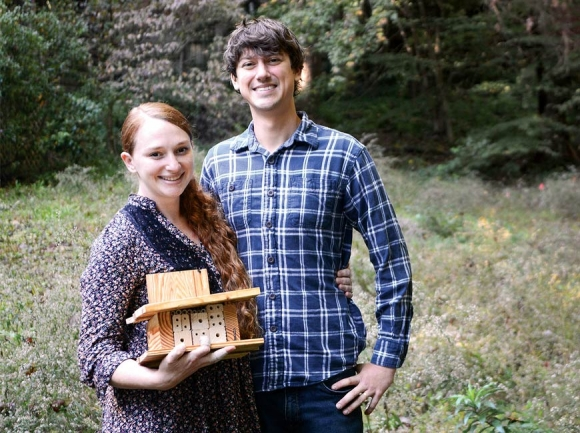 Jill Jacobs and her husband Brannen Basham hold up one of their handmade bee houses amid flowering native plants at their home in Waynesville. Holly Kays photos