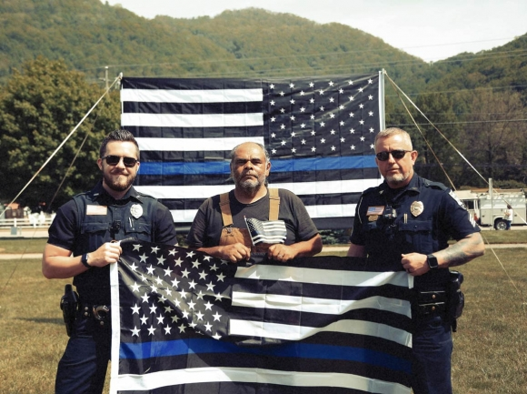 Maggie Valley police officers pose in front of the Back the Blue flag. Jeffrey Delannoy photo