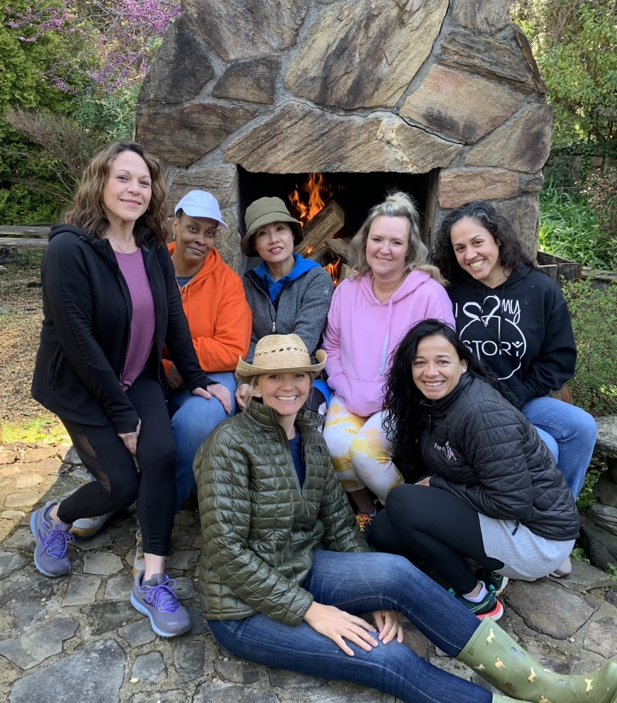 Participants pose for a quick photo by the Franklin-based Special Liberty Project's outdoor fireplace with co-founder Jessica Merritt (sitting) during SLP's first monthly Vitality Retreat for Gold Star Widows.