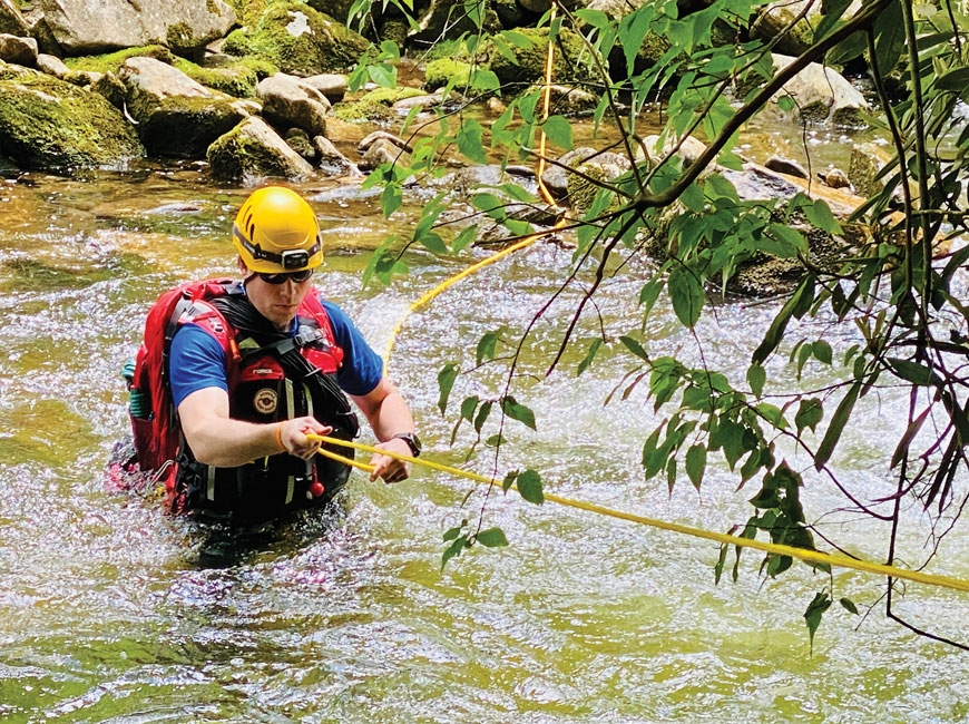 Kyle James, field team lead for Haywood Search and Rescue, carefully crosses a tributary of the West Fork Pigeon River. Nancy East photo