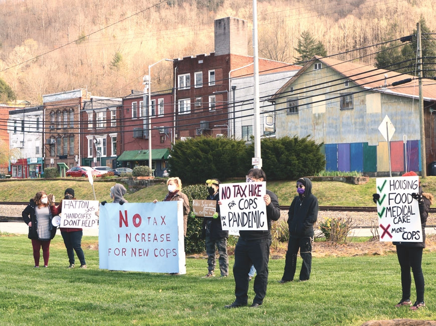 Protestors hold signs opposing a plan to increase taxes to fund additional police officers during a public hearing on a different topic the board held at Bridge Park April 1. Holly Kays photo