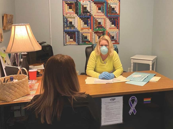 Julia Freeman, executive director of REACH of Haywood County, assists a client while wearing a face mask to prevent potential spread of COVID-19. Donated photo