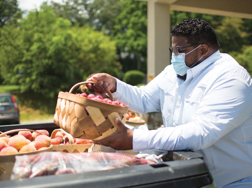 Pastor Rubi Pimentel of Hendersonville Spanish Church unloads produce from a local farm to feed community members in need. Photo by Colby Rabon