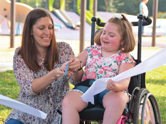 Maggie Garrett (right) helps Haywood County Schools Physical Therapist Mary Beth Brown cut the ribbon on Waynesville's new all-abilities playground. Cory Vaillancourt photo