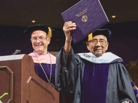 The late Jerry Wolfe, a Beloved Man in the Eastern Band of Cherokee Indians, holds his honorary doctorate from WCU while standing alongside Chancellor Belcher in May 2017. WCU photo