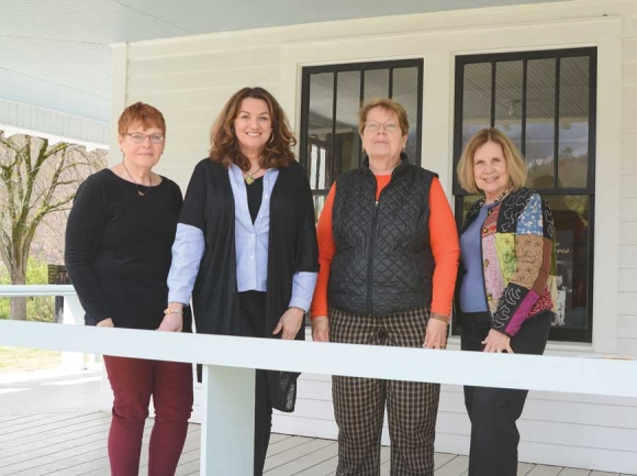 Appalachian Women's Museum board members stand on the porch of the building in Dillsboro. Pictured left to right are treasurer Debi Sullivan, past president Cathy Monteith Busick, current president Sharon Sullivan and vice president Marty Greeble.