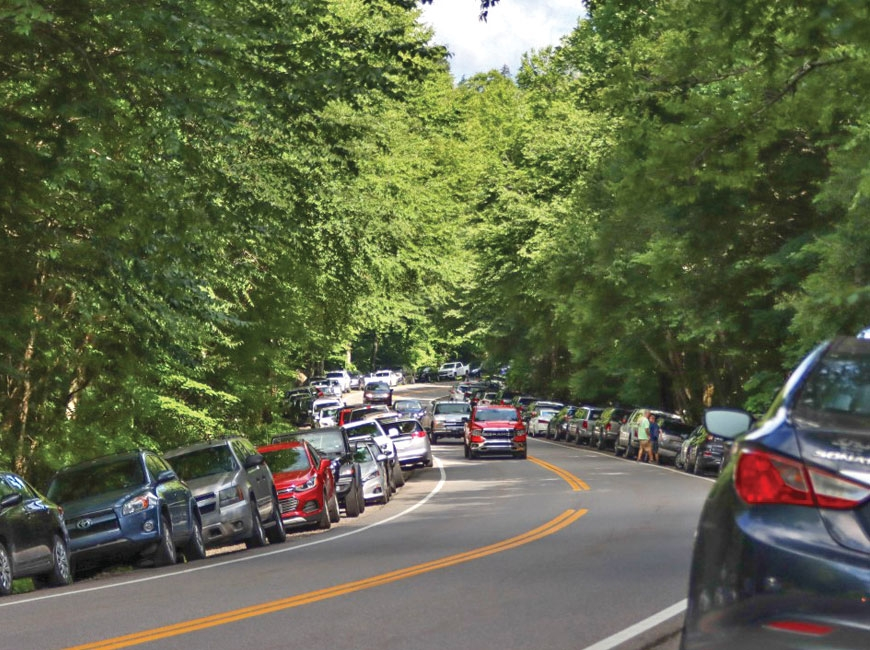 On a Saturday in July 2020, cars line both sides of Newfound Gap Road near the trailhead for Alum Cave Trail. NPS photo
