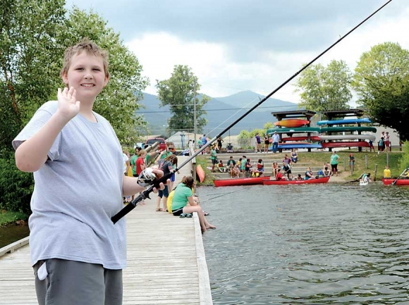 A camper waves from the dock at Lake Junaluska after an afternoon of fishing and canoeing. Holly Kays photo