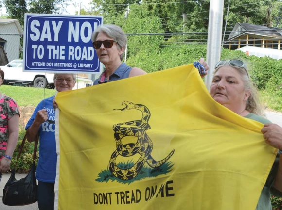 Protestors gather outside the Sylva Town Hall in advance of the meeting, carrying signs and distributing 'Say No To The Road' bracelets. Holly Kays photo