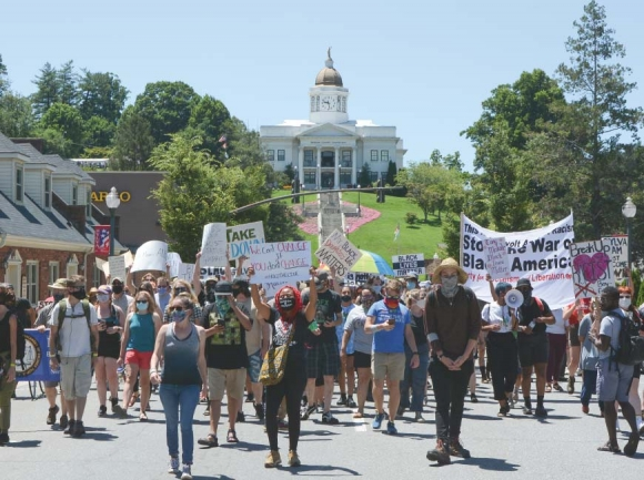 Protestors walk below the hill where the statue perches during a July 2020 march opposing the monument. Holly Kays photo