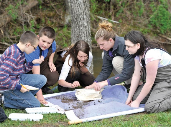 Western Carolina University senior Brittany Timpson shows an inquisitive group of elementary students in the Watershed Moments program a macro invertebrate. Inset, below: Liam Tormey has been an avid participant in the program.