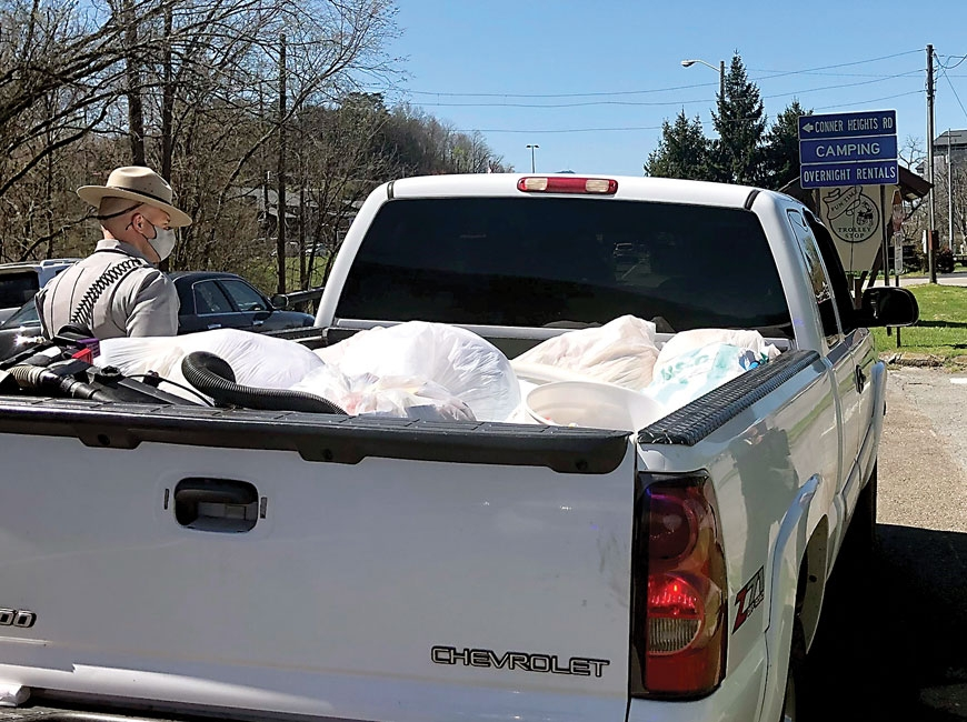 A park ranger speaks with the driver of a truck hauling unsecured garbage. NPS photo