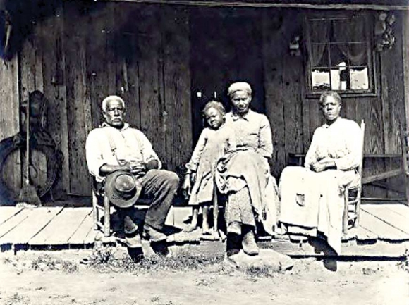 In a photo taken between 1890 and 1903, an African-American family sits on a front porch in the Great Smokies region. W.O. Garner Photograph Collection