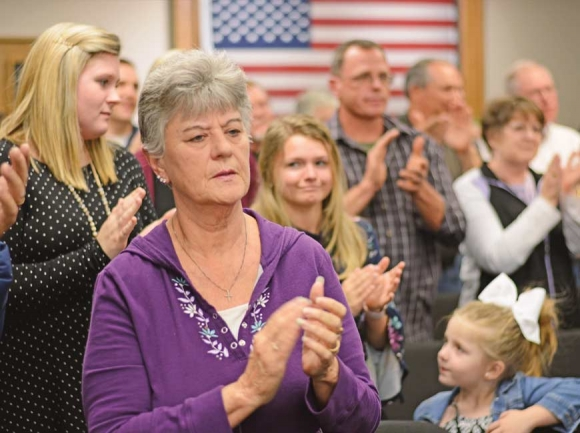 Members of the community opposed to Sunday morning alcohol sales applaud following public comment from one of the many anti-alcohol speakers who spoke during a public hearing March 19. Holly Kays photo