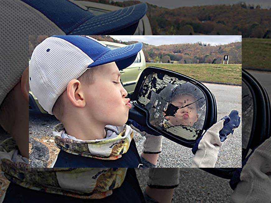 A young volunteer makes a face in a reflective piece of trash. Donated photo