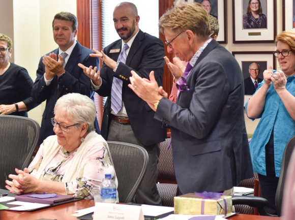 Trustees and university faculty applaud former Principal Chief Joyce Dugan (seated) during her last board meeting. Holly Kays photo