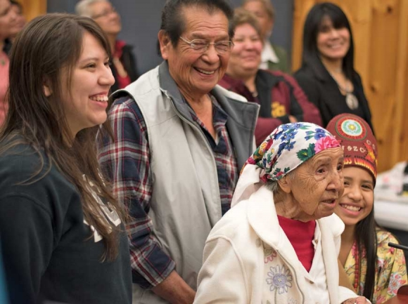 Amanda Swimmer's family members, standing around her, laugh as she cracks a joke during her remarks following Tribal Council's decision to name her a Beloved Woman. Holly Kays photo