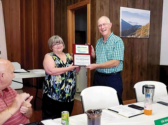 Mike Fitzgerald accepts a plaque recognizing his years of service form Town Clerk Debbie Coffey during his last meeting June 14. Donated photo