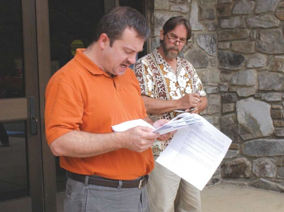 In this 2009 photo, Rick Boyd conducts a foreclosure sale of two large tracts owned by developer Legasus outside the Jackson County courthouse while concerned citizen Thomas Crowe follows along.