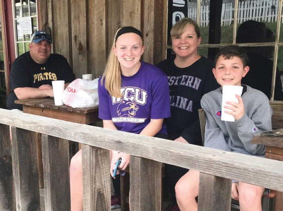 Junior nursing student Ashlee Owens (in purple) enjoys some takeout barbecue with          her mother, uncle and cousin after an unexpectedly early move-out from Western Carolina University. Holly Kays photo